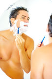 Shaving. Handsome man shaving in the bathroom royalty free stock photography
