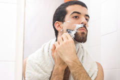 Shaving. Man shaving and looking to the mirror stock photo