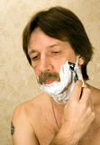 Shaving. The man has a shave with a razor Stock Photo