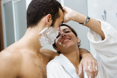 Shaving. Morning routine: the guy shaving and the girl (trying to) apply her make-up Stock Image