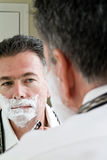 Shaving 2. A man looking in the mirror in the process of shaving Stock Image