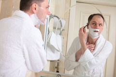 Shaving. Man shaving his cheek hair using safety razor Stock Photography