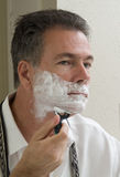 Shaving 3. A man looking in the mirror in the process of shaving Royalty Free Stock Photos