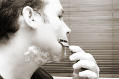 Shaving. Man shaving his beard off. Looking in the mirror. Sepia tone Stock Images