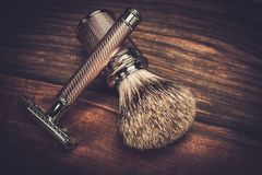 Shaving accessories. Safety razor and shaving brush on a wooden background Royalty Free Stock Photo