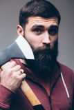 Shaving with axe. Confident young bearded man carrying a big axe Stock Photo