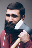 Shaving with axe. Portrait of Confident young bearded man carrying a big axe Royalty Free Stock Photography