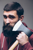 Shaving with axe. Portrait of Confident young bearded man carrying a big axe on shoulder and looking at camera Stock Photography