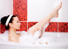 Shaving in the bath. Young slim woman shaving legs in the bathroom Stock Image