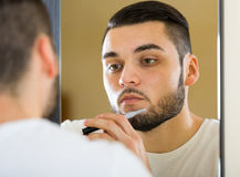Shaving beard with trimmer Royalty Free Stock Image