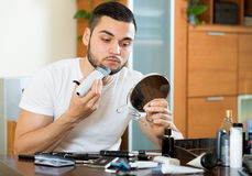 Shaving beard with a trimmer Stock Photos