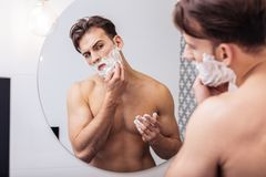 Sexy handsome man shaving his face before breakfast. Shaving before breakfast. Sexy handsome dark-haired man shaving his face before breakfast at home royalty free stock photography