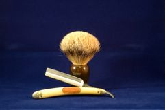 Shaving brush and razor. A closeup view of a genuine badger fur shaving brush with a brown plastic handle, isolated on a blue background with an antique straight Royalty Free Stock Photography