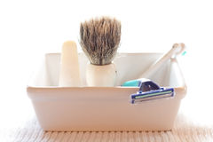 Shaving brush and razor in a soap diah. Stock Photos
