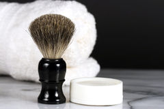 Shaving Brush & Soap. A men's badger bristle shaving brush and round cake of shaving soap on marble counter top with rolled towel in background Royalty Free Stock Photos