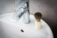 Shaving brush on the washbasin in the bathroom Stock Photo