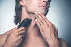 Shaving with electric razor. royalty free stock photography
