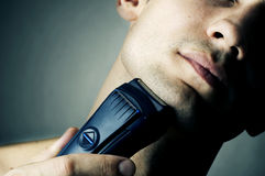 Shaving by electric shaver. Fashion portrait of male chin and electric shaver Stock Photos
