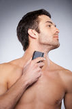 Shaving with electric shaver. Royalty Free Stock Image