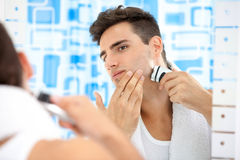 Shaving by electric shaver. Young man shaving by electric shaver Royalty Free Stock Photography