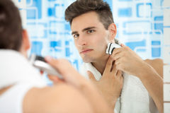 Shaving by electric shaver Royalty Free Stock Photos