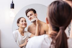 Couple having much fun putting shaving foam on face of husband. Shaving foam. Couple having much fun while putting shaving foam on face of handsome sexy husband stock photography