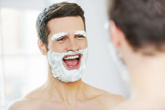 Shaving with fun. Rear view of playful young man with shaving cream on his face smiling while standing in front of the mirror stock photography