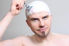 Shaving head. Young man with razor shaving head Stock Photography