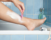 Shaving her legs Stock Images