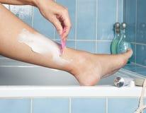 Shaving her legs Stock Images