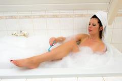 Shaving her legs Stock Image