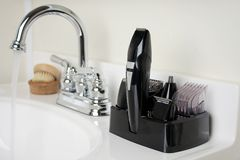 Shaving Kit in Bathroom. Shaving kit on sink next to faucet with running water Stock Photos