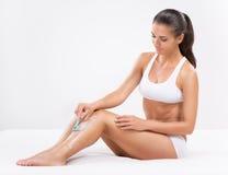 Shaving leg. Beautiful young woman shaving her legs Stock Photos