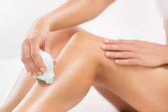Shaving legs Royalty Free Stock Photo