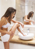 Shaving legs. Busy woman shaving legs in sink of bathroom royalty free stock image