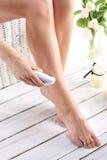 Shaving legs Royalty Free Stock Photos