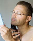 Shaving man. Handsome man shaving with electric razor, looking into mirror Royalty Free Stock Photography