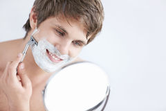 Shaving a man Stock Images