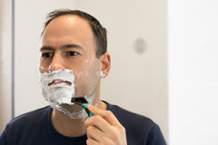 Shaving Man on foam with razor mirror in bathroom Stock Photos