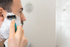Shaving Man on foam with razor mirror in bathroom Stock Image