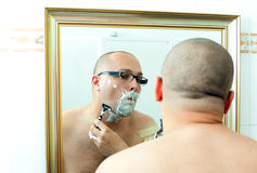 Shaving man in glasses Stock Images
