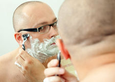 Shaving man in glasses Royalty Free Stock Images