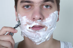 Shaving man on a gray background. Young man shaving with a razor in the morning Stock Image