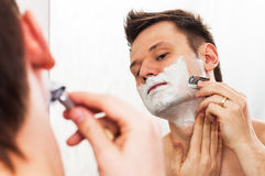 Shaving man in the mirror. Handsome 30 years old man shaves in front of the mirror with adjustable Double edged safety razor stock photography
