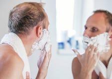 Shaving man near the bathroom mirror Royalty Free Stock Photos