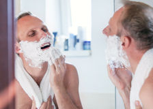 Shaving man near the mirror Royalty Free Stock Photography