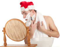 Shaving man in red Christmsa hat Royalty Free Stock Image