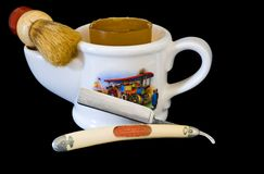 Shaving Mug, Brush and Straight Razor. Close up of a white antique shaving mug with a handle on one end, a brush holder on the other, a 1890s scene on the side Stock Image