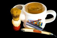 Shaving Mug, Straight Razor and Brush. Close up of a white antique shaving mug with a handle on one end, a brush holder on the other, a 1890s scene on the side Royalty Free Stock Photos