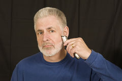 Shaving Off Beard. A middle aged man begins the process of shaving off his beard Stock Photography